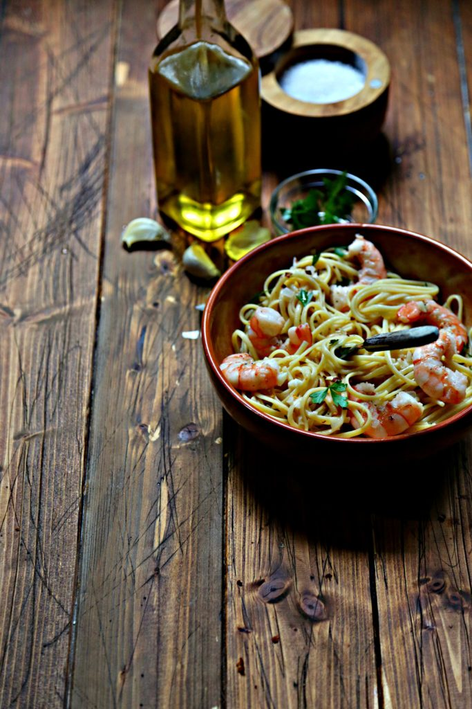 linguine and shrimp in brown bowl with fork. Bottle of olive oil, garlic cloves, small glass bowl of parsley in background.