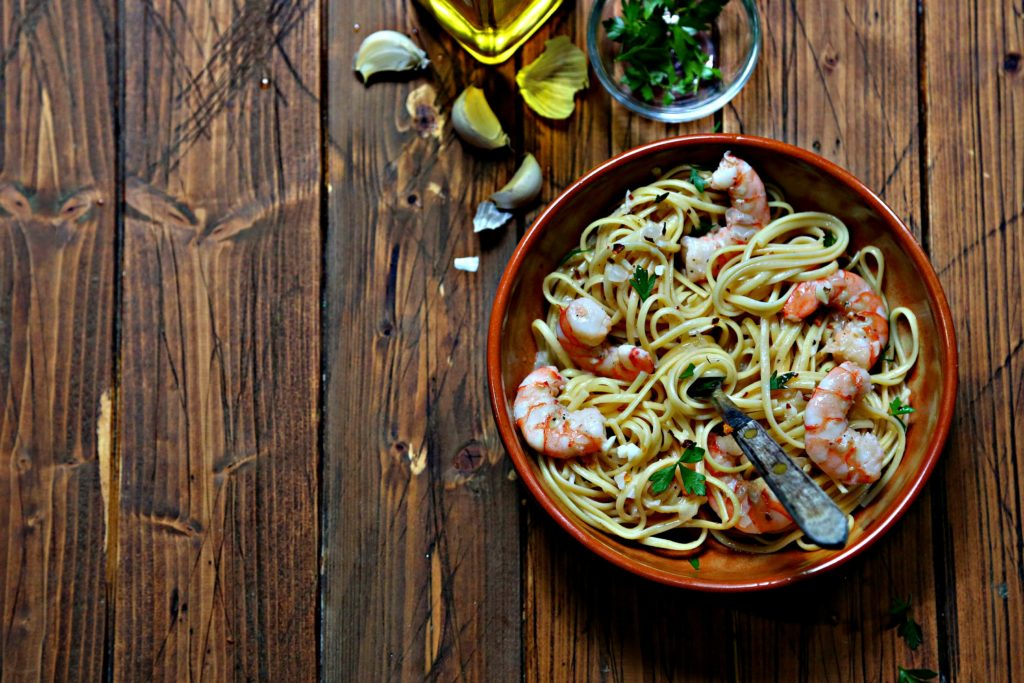 shrimp linguine in brown bowl with fork. Garlic cloves, small bowl of parsley and bottle of olive oil in background.