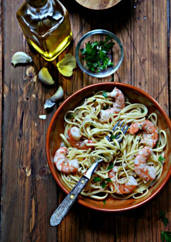 shrimp linguine in brown bowl with fork. Garlic cloves, small glass bowl of parsley and olive oil bottle in background.