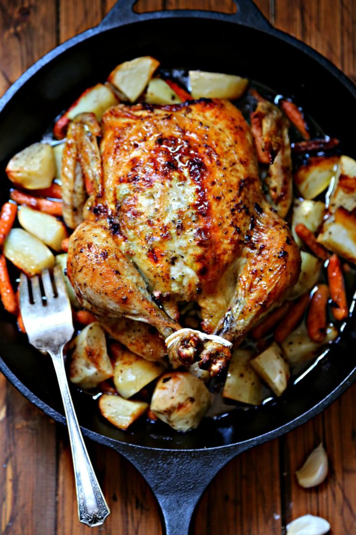 closeup of roasted chicken in cast iron skillet with potatoes and carrots. Fork to left of chicken.