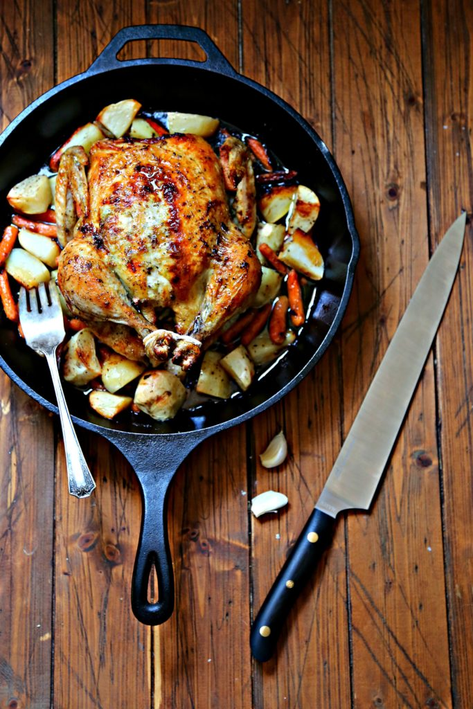 Roasted chicken in cast iron skillet surrounded by potatoes and carrots. Carving knife and cloves of garlic to right of skillet.