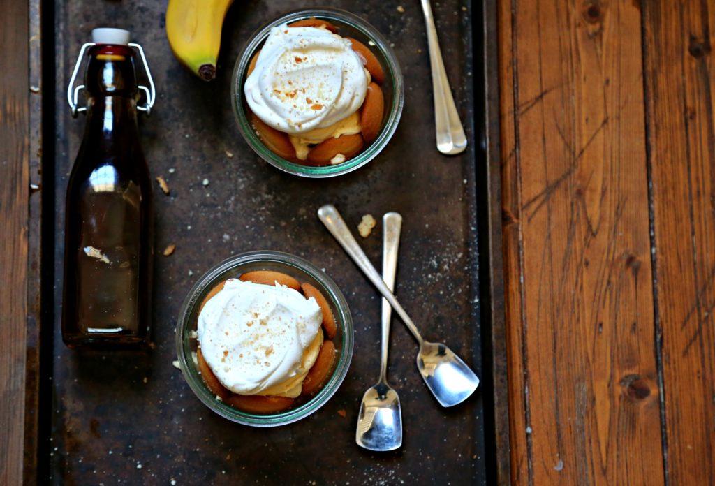 2 jars of banana pudding on baking sheet. Spoons, bananas and vanilla extract to side.