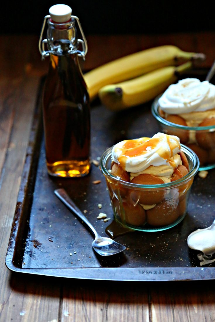 2 glass jars of banana pudding. Topped with whipped cream and caramel sauce sitting on baking sheet. Spoons, bottle of vanilla extract and bananas to side.