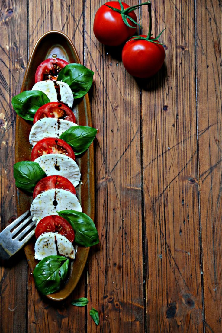 Slices of tomatoes, mozzarella and fresh basil on brown oval tray. Serving fork to side and tomatoes in background.