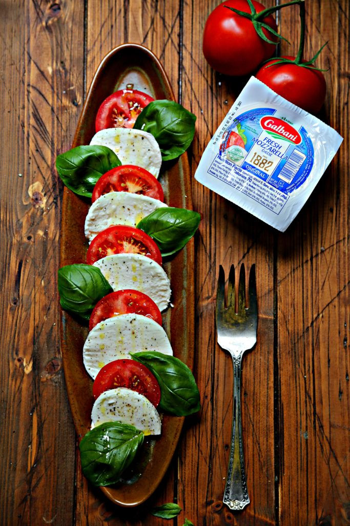 sliced tomatoes, mozzarella and basil on brown oval tray. Serving fork, ball of mozzarella and tomatoes to side.