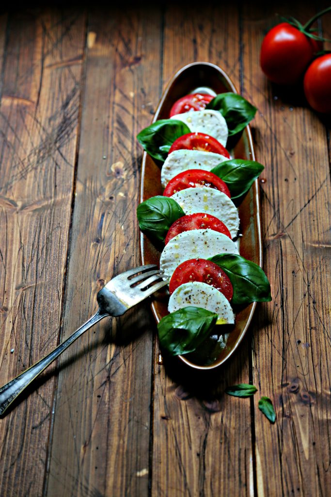 Slices of tomatoes, mozzarella and basil on brown oval tray. Serving fork to side.