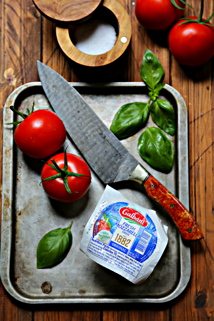 whole tomatoes, basil leaves, ball of mozzarella and knife on baking sheet. Salt cellar and tomatoes in background.