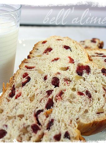 slice of Cranberry Walnut Celebration Bread with glass of milk behind.