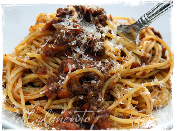 spaghetti and bolognese sauce on white plate with fork.