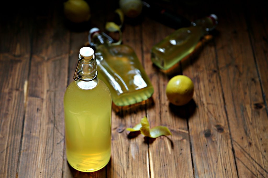 bottles of homemade limoncello surrounded by lemons and lemon peels