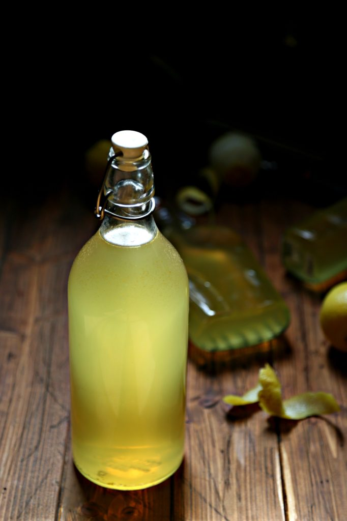 bottles of homemade limoncello with lemon peels surrounding