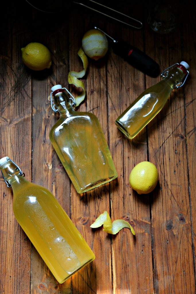 bottles of limoncello surrounded by lemons, vegetable peeler and lemon peels