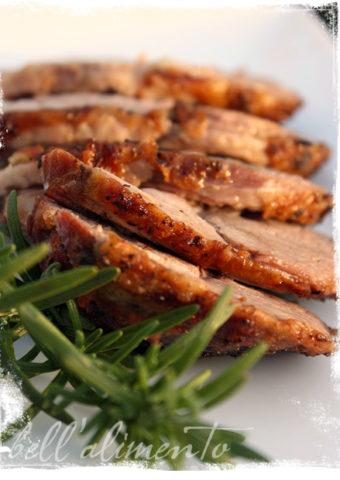 sliced lamb on white platter with fresh rosemary