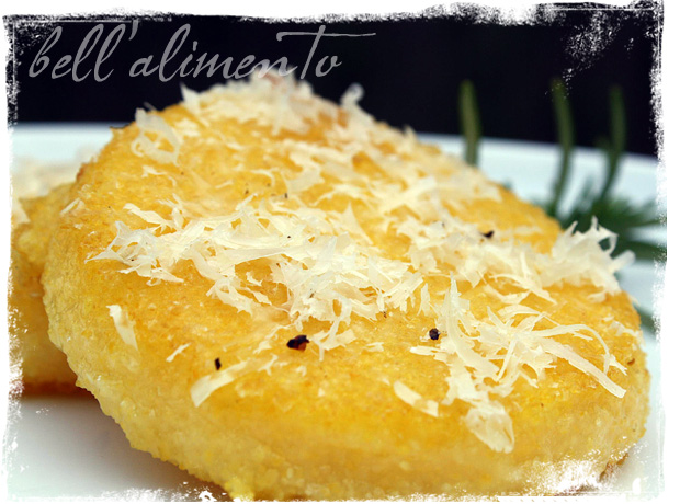 Polenta Cakes on white plate with grated cheese on top.