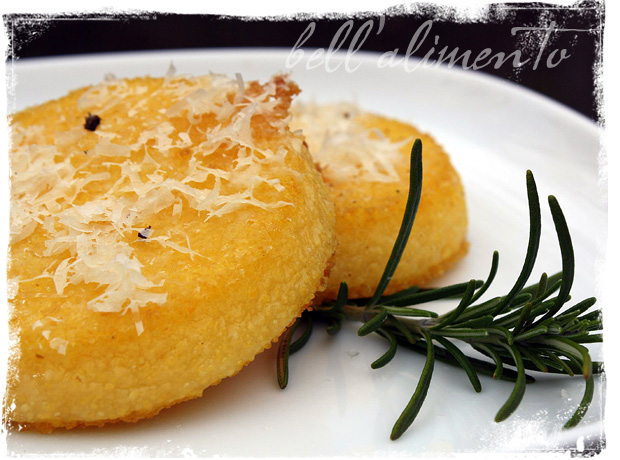 Polenta Cakes with grated cheese sitting on white plate. Garnished with a sprig of rosemary.