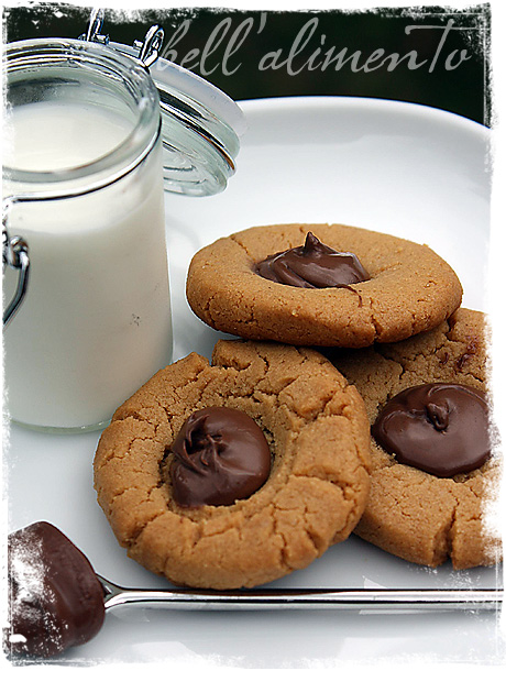 Three thumbprint cookies on white plate. Glass of milk to side. Spoon with Nutella in front of cookies.