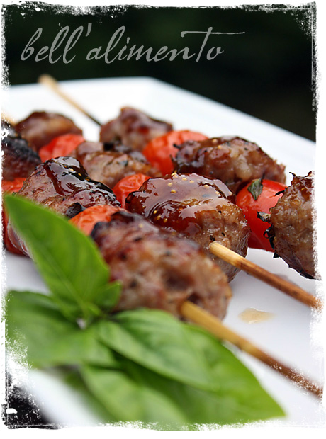 Sausage Kebabs Glazed with Balsamic and Fig Preserves on white plate.