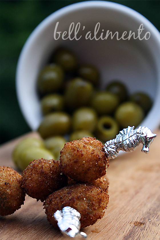fried olives on metal cocktail pick. White ramekin of green olives behind.