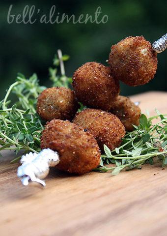 fried olives skewered on metal toothpick.