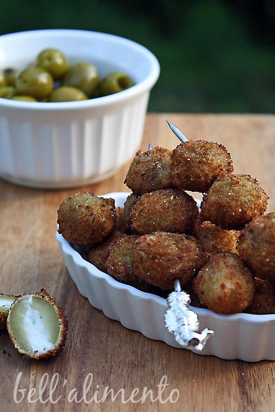 white ramekin of green olives. White ramekin with fried olives.