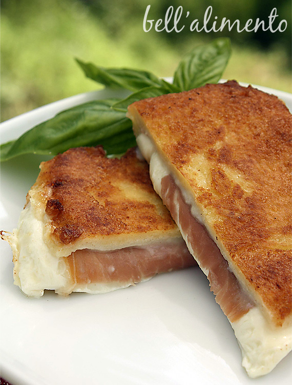 Fried Mozzarella and ham sandwich cut in half on white plate garnished with fresh basil.