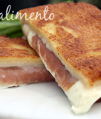 Grilled ham and cheese on white plate garnished with fresh basil.