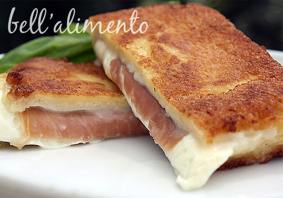 Grilled ham and cheese sliced in half on white plate. Fresh basil leaf behind sandwich.