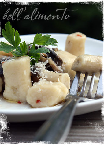 plate of Gnocchi with Mushroom Sauce. Fork in one piece of gnocchi.