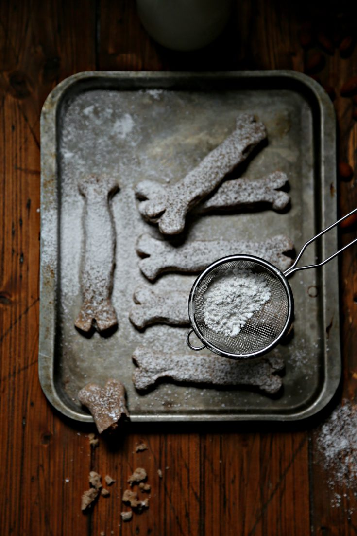 Bones of the Dead Cookies on baking sheet with sieve of powdered sugar above