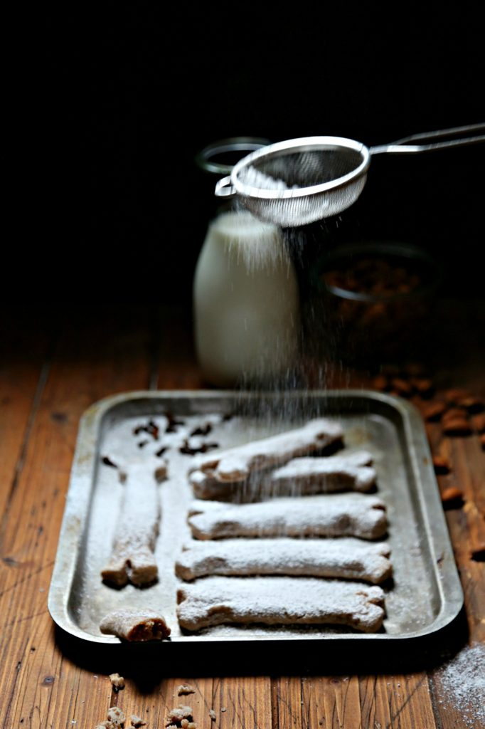 Bones of the Dead Cookies on baking sheet, carafe of milk, powdered sugar snowing above it.