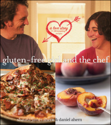 Cover of gluten free girl and the chef cookbook. Man and woman pizza in front and peaches to right.