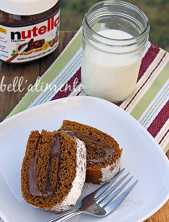 Two slices of pumpkin roll on white plate with fork. Stripe napkin under plate. Glass of milk and jar of Nutella in background.