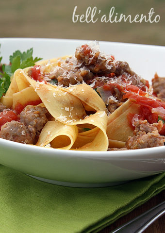 Pappardelle pasta with Sausage in white bowl. Green napkin under bowl.