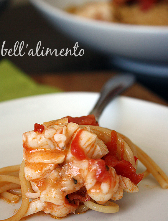 pasta with lobster around fork sitting on white plate.
