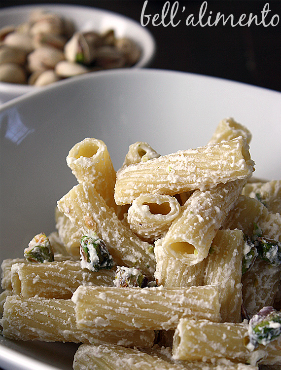 Close up of white bowl of Macaroni with Ricotta pasta. Small white bowl of pistachios in background.