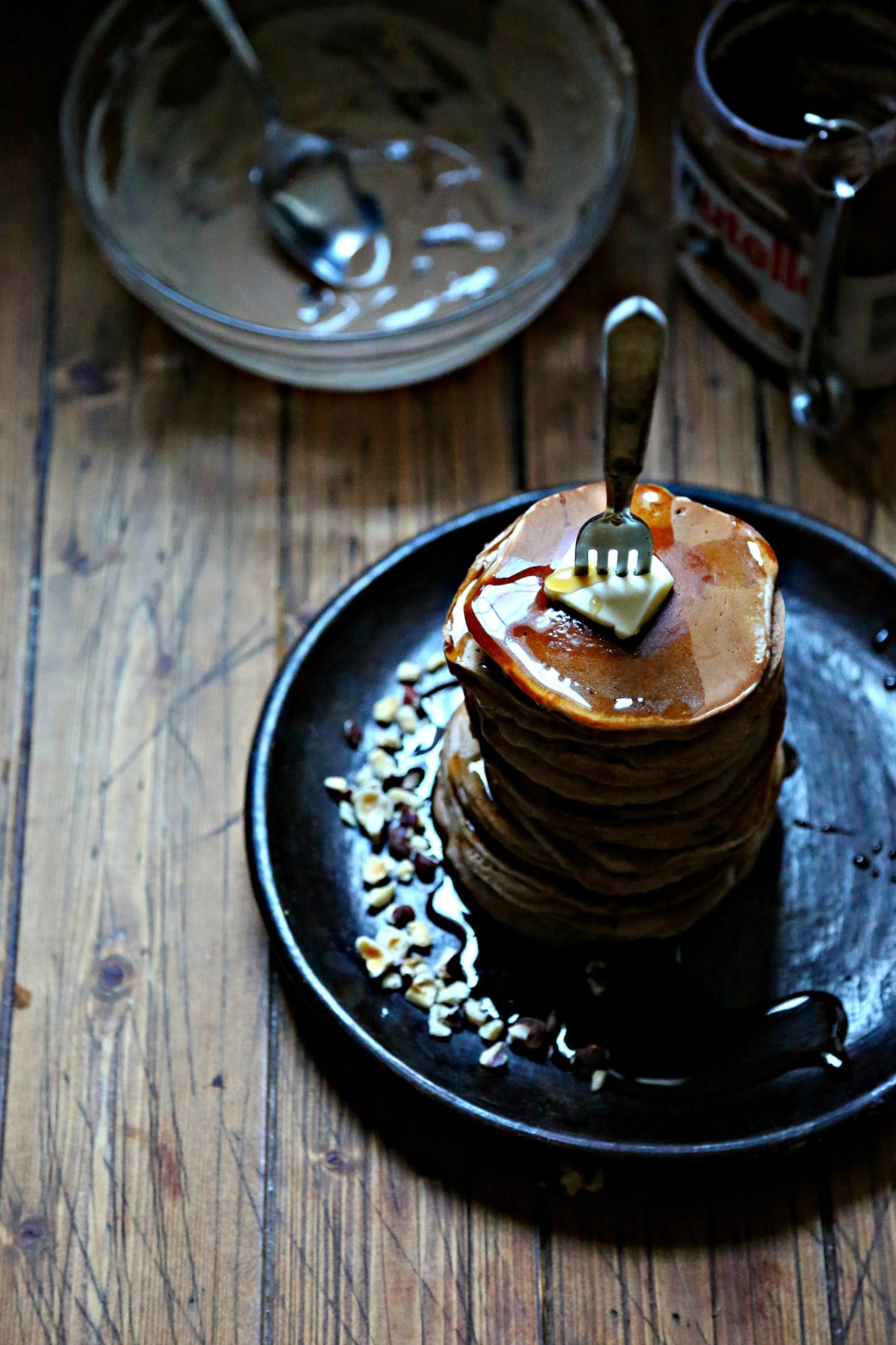 Stack of Nutella pancakes with fork going through, messy bowl of batter behind
