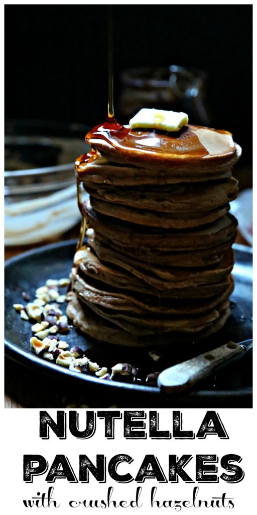Stack of Nutella pancakes on plate with butter, syrup and crushed hazelnuts