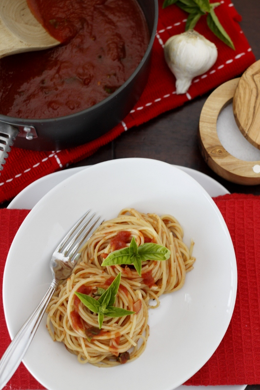 Spaghetti with Salsa di Pomodoro - Tomato Sauce on white plate. Pot of sauce on red kitchen towel behind. Salt cellar to side.