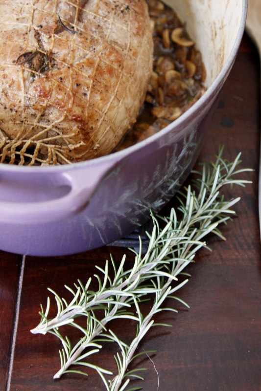 braised pork roast in cassis le creuset with fresh rosemary sprigs to side.