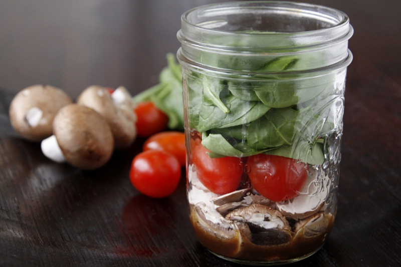 Small glass jar with spinach, cherry tomatoes, mushrooms and balsamic vinaigrette. Mushrooms, cherry tomatoes in background.