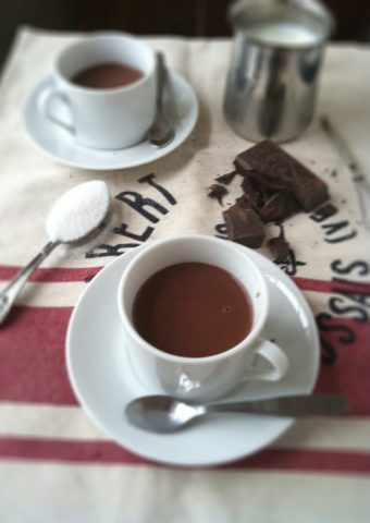 cup of Italian hot chocolate with chocolate, milk and spoons surrounding