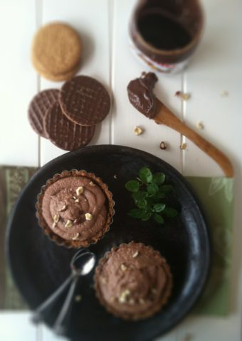 2 nutella mascarpone chocolate tarts on brown plate with small spoons. Cookies, and jar of nutella with wooden spoon behind.