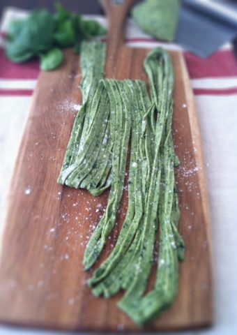 fresh spinach pasta on a wooden board with fresh spinach and pasta dough on pastry cutter on side