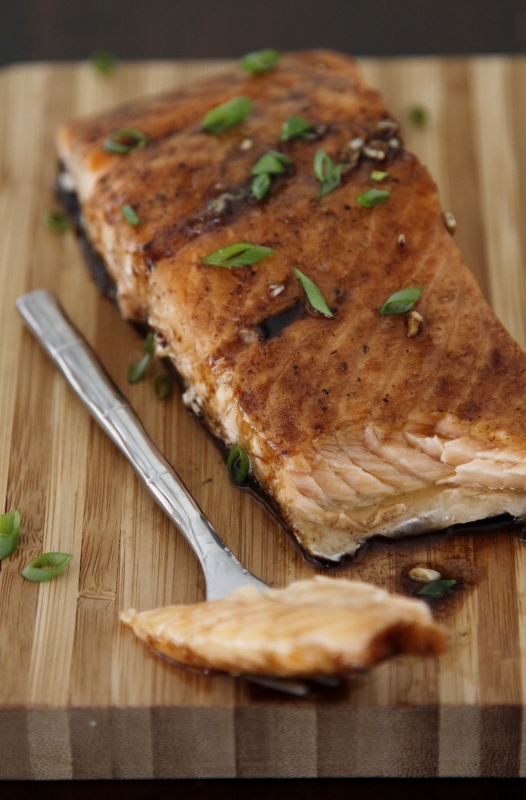 Piece of Maple Balsamic Glazed Salmon garnished with green onions on cutting board. Fork with piece of fish to side.