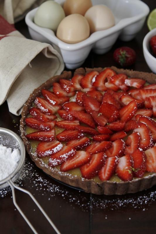 strawberry tart, sieve with powdered sugar, container of eggs, napkin and various strawberries around tart.