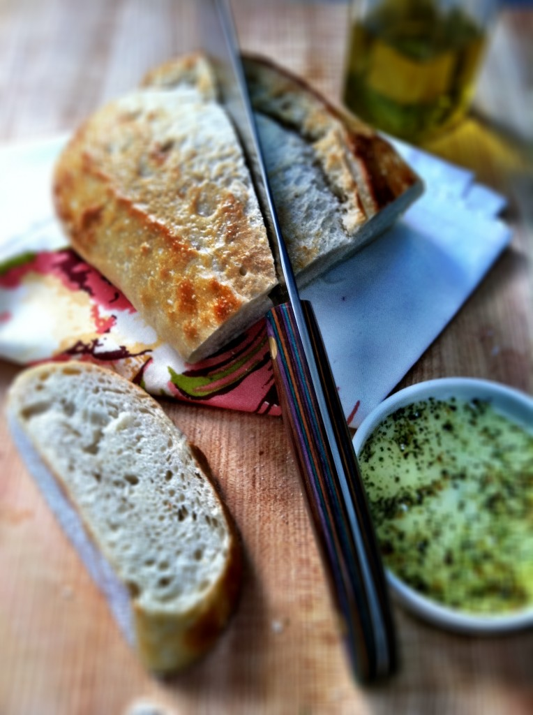 homemade bread with bread knife and dipping sauce