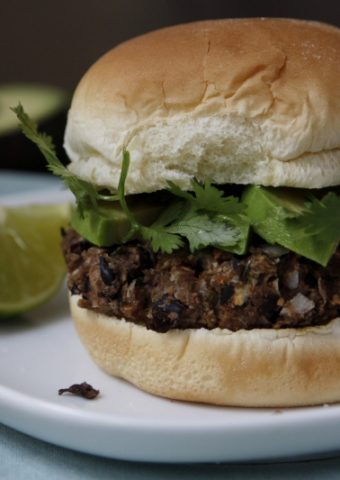 black bean veggie burger on white plate with lime wedge. Blue napkin under plate. Avocado half in background.