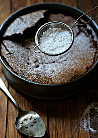 chocolate cake with metal sifter of powdered sugar above. Serving piece to side.