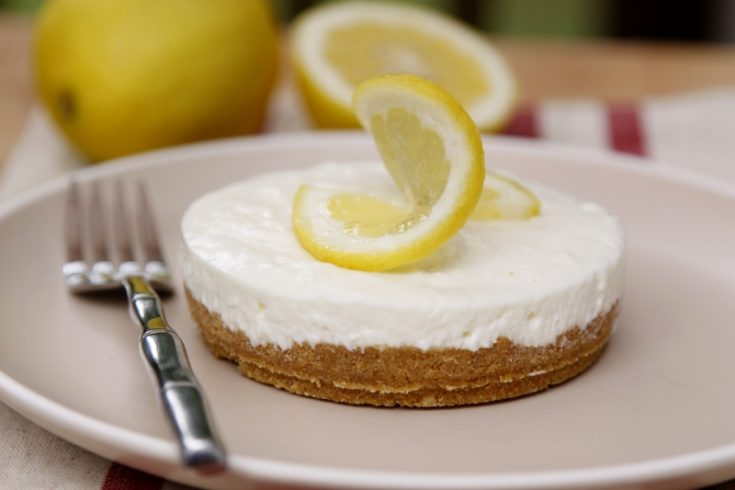 no bake cheesecake with lemon slice on plate with fork.