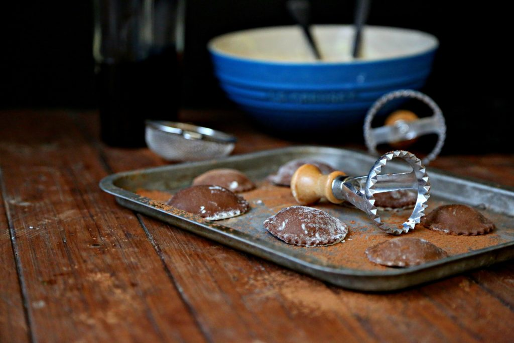 chocolate ravioli on baking sheet with ravioli stamp and bowl of filling